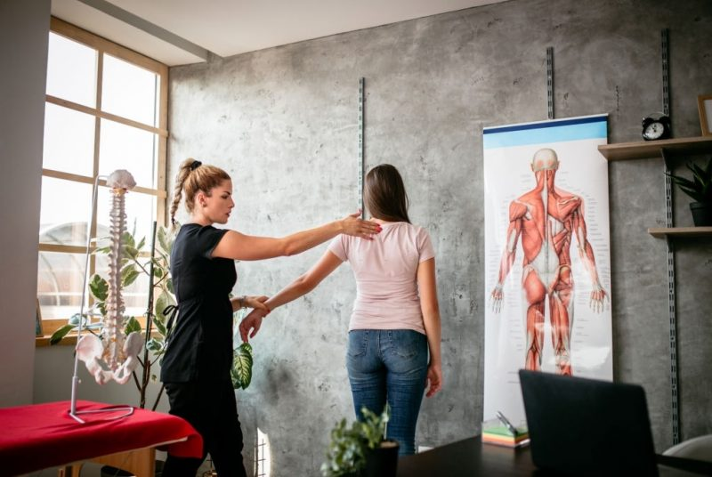 Massage therapy instructor showing anatomy on live model in massage school
